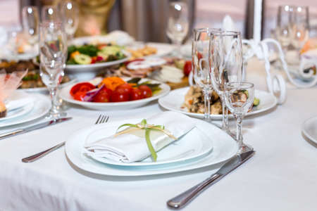napkin on a plate on the holiday table served with various dishes Stock Photo