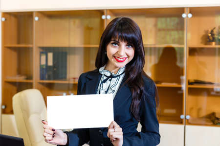 notecard: happy woman shows empty white card in office
