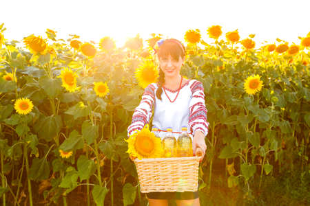 basket embroidery: Smiling girl in embroidery holding a basket with sunflower oil on a field
