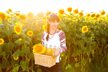 basket embroidery: Smiling woman in embroidery holding a basket with sunflower oil on a field