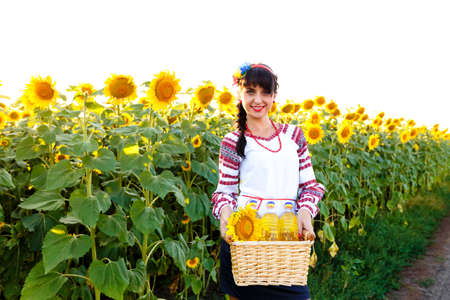 basket embroidery: Smiling girl in embroidery holding a basket with sunflower oil