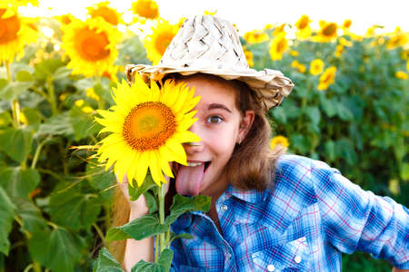 tongues: Joyful girl with sunflowers in a wicker hat showing tongue