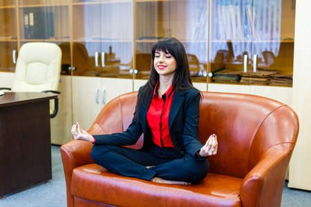 lotus position: Nice smiling businesswoman sitting on a sofa in the lotus position