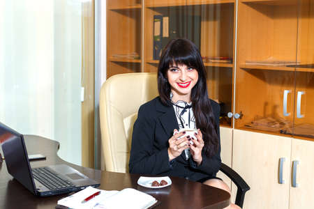 Beautiful smiling woman in office holding a cap of coffee
