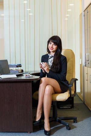 falda corta: Mujer bonita en un caf� de consumici�n de la falda corta en la oficina