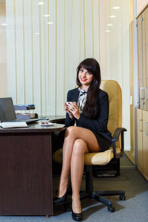 sexy office girl: Pretty woman in a short skirt drinking coffee in the office