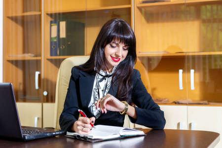 オフィスで働くと、自分の時計を見て笑顔の女性 写真素材