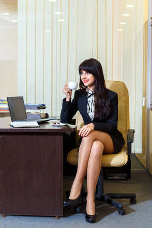 businesswoman legs: Beautiful woman in a short skirt drinking coffee in the office