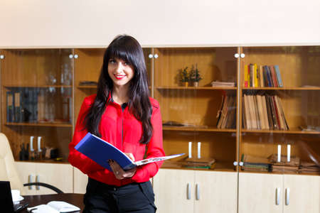 expect: Smiling young woman in a red blouse with a folder of documents in the office