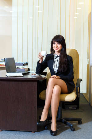short skirt: attractive woman in a short skirt drinking coffee in the officev