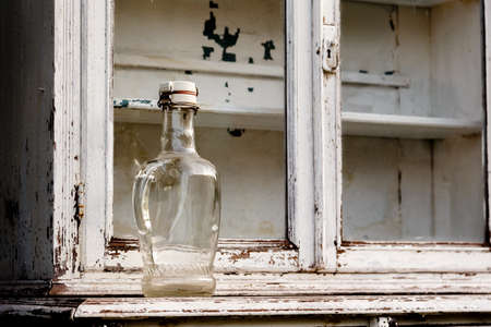 old furniture: empty glass bottle on an old white kitchen cabinet Stock Photo