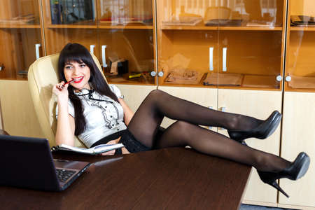 Beautiful girl sitting in an office at a desk with his legs on the table