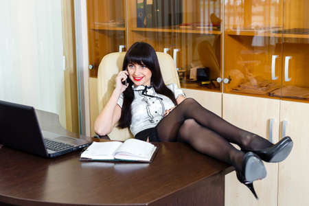 Young pretty woman speaks by phone in office Stock Photo