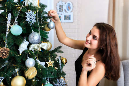 decorates: Beautiful woman in a black dress decorates a Christmas tree Stock Photo