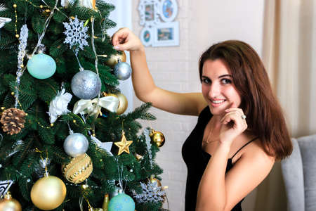 decorates: Beautiful girl in a black dress decorates a Christmas tree