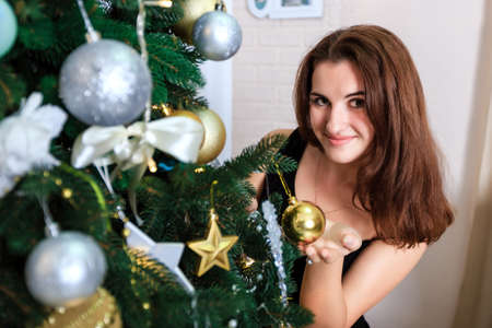decorates: Smiling girl in a black dress decorates a Christmas tree