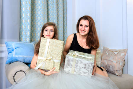 1 2 month: Two girls sitting on the sofa with a christmas gifts Stock Photo