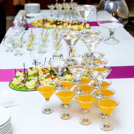banket: Pyramid of glasses with drinks and wine on banquet table