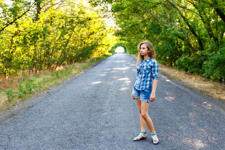 blue plaid: beautiful girl in blue plaid shirt walking on an empty road between green trees