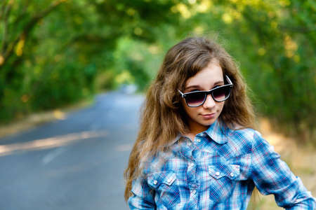 blue plaid: beautiful girl in black sunglasses and blue plaid shirt on the road between the green trees