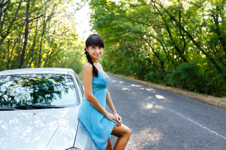 sexy girl posing: Sexy young woman standing on the road near the white car