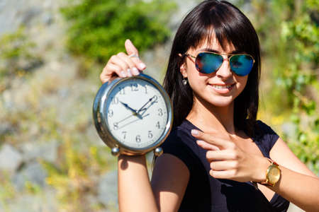 Beautiful girl in a black top and sunglasses showing a clock. Focus on a face, concept of time to travel Stock Photo