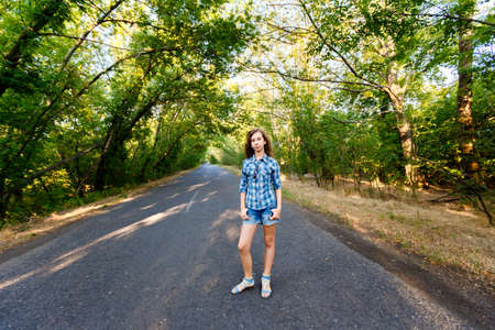 blue plaid: beautiful girl in blue plaid shirt standing on an empty road between green trees