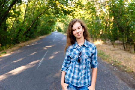 blue shirt: beautiful girl in blue plaid shirt standing on an empty road between green trees