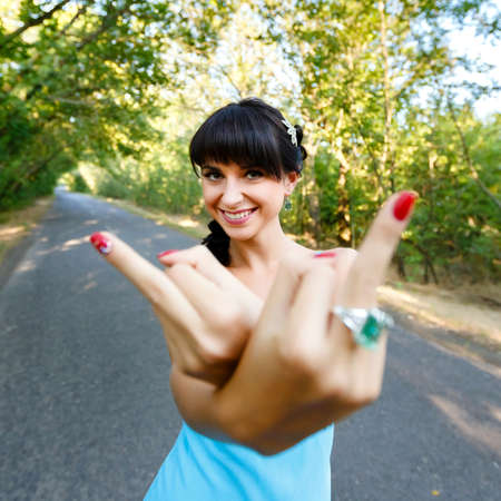 off day: smiling woman in blue dress showing  two hands with middle finger, fuck you off sign. Sunny day, on a road with green trees. Swag.