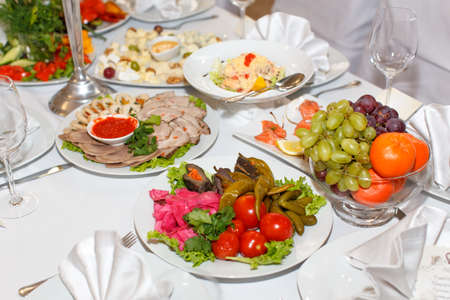 banket: Cutting meat, pickles, fruit on a festive table