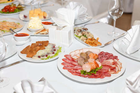 banket: Sausages, cold cuts, dishes on a white banquet table in restaurant