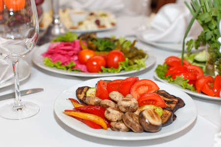 banket: Marinated mushrooms, tomatoes, peppers and dishes on the banquet table Stock Photo