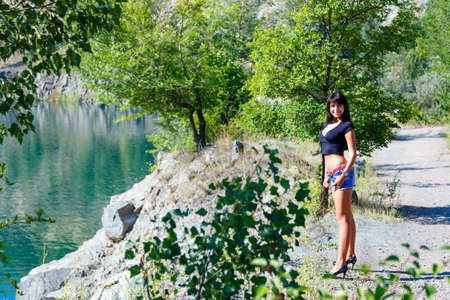 decolette: beautiful girl in a black top and denim shorts standing on the shore of a mountain river