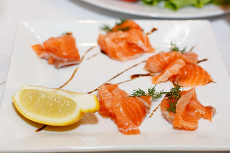 banket: Sliced pieces of salmon and lemon on a white plate closeup