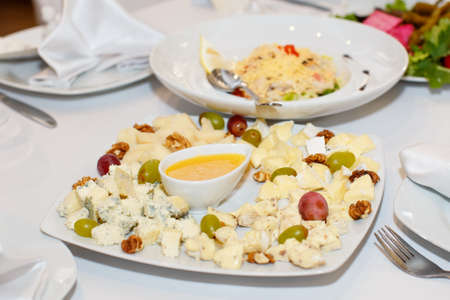 banket: Sliced cheese, grapes, honey on a white plate on the holiday table in restaurant