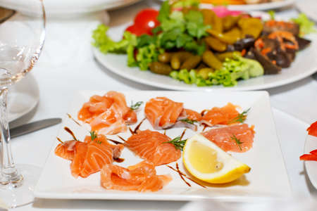 banket: Sliced pieces of salmon and lemon on a white plate in a restaurant Stock Photo