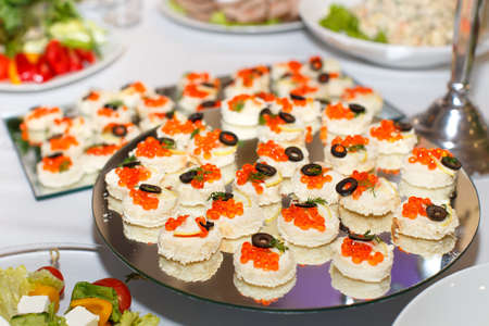 banket: Appetizers with red caviar on a mirror plate on a festive table in restaurant Stock Photo