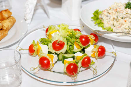banket: Canapes with tomatoes, cucumbers, cheese and greens on a banquet table