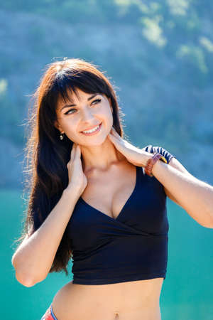 decolette: beautiful girl standing on the shore of a mountain lake at sunny sammer day Stock Photo