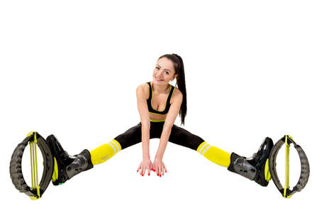 decolette: smiling young woman brunette with long hair  in a kangoo jumps shoes sitting  legs apart. Isolated on white background in studio. Shot at wide angle