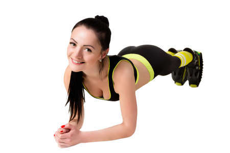 decolette: slender smiling girl in kangoo jamps shoes doing plank exercise, looks at the camera. Isolated on white background in studio