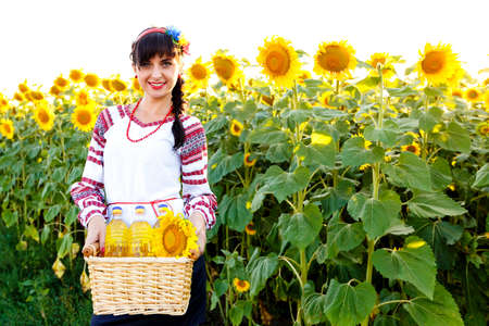 basket embroidery: Smiling woman in embroidery holding a basket with sunflower oil