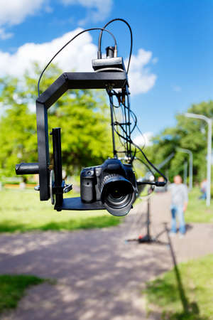 photocamera: photocamera on the platform close-up and blurred videographer, use camera crane in the park at summer day Stock Photo
