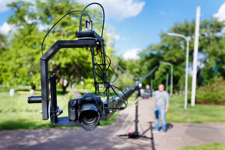 photocamera on the platform close-up and blurred videographer, use camera crane in the park at summer day Stock Photo