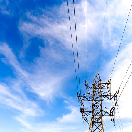 electrical high voltage tower with cables on cloudy blue sky background. copy space