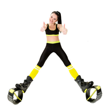 smiling young woman brunette with long hair in a kangoo jumps shoes showing fingers up, sign OK. Isolated on white background in studio. Shot at wide angle Stock Photo