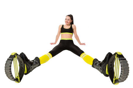 legs apart: smiling young woman brunette with long hair in a kangoo jumps shoes sitting legs apart. Isolated on white background in studio. Shot at wide angle