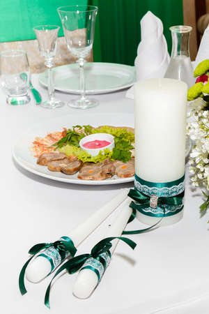 banket: Beautiful white candles with green ribbon on a wedding decorated table. Stock Photo