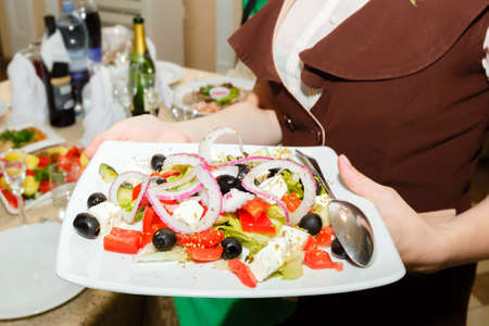 banket: Waitress holding a plate with salad, served festive table at restaurant