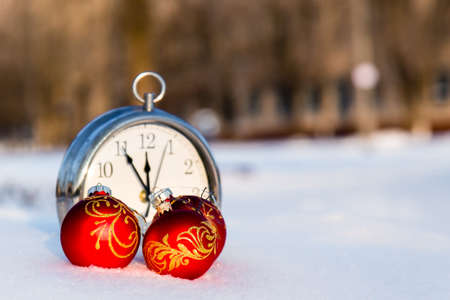 Three red christmas balls and wath on a snow. New Year greeting card concept. Copy-space